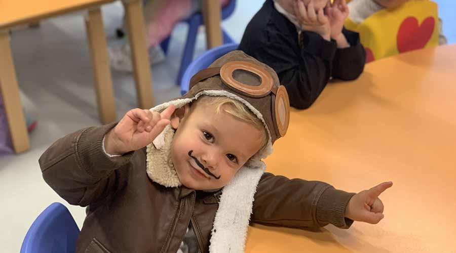Niño disfrazado de aviador levantando el dedo
