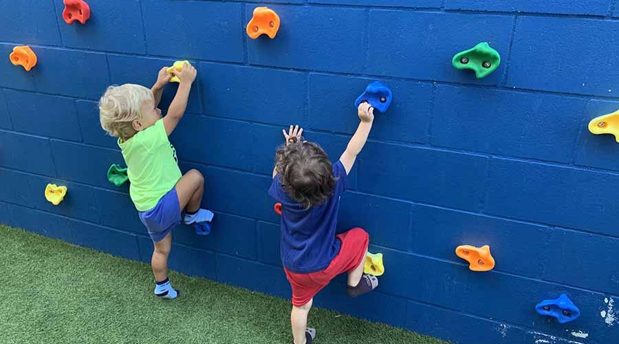 Niño y niña de un año escalando un rocódromo