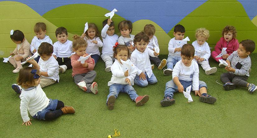 Niños de 1 año vestidos con tejanos y camiseta blanca en el suelo