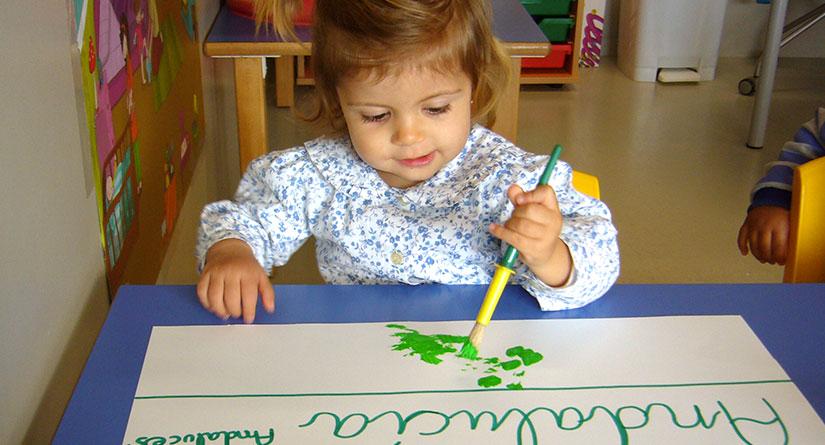 Niña de 1 o 2 años pintando en verde sobre una cartulina blanca